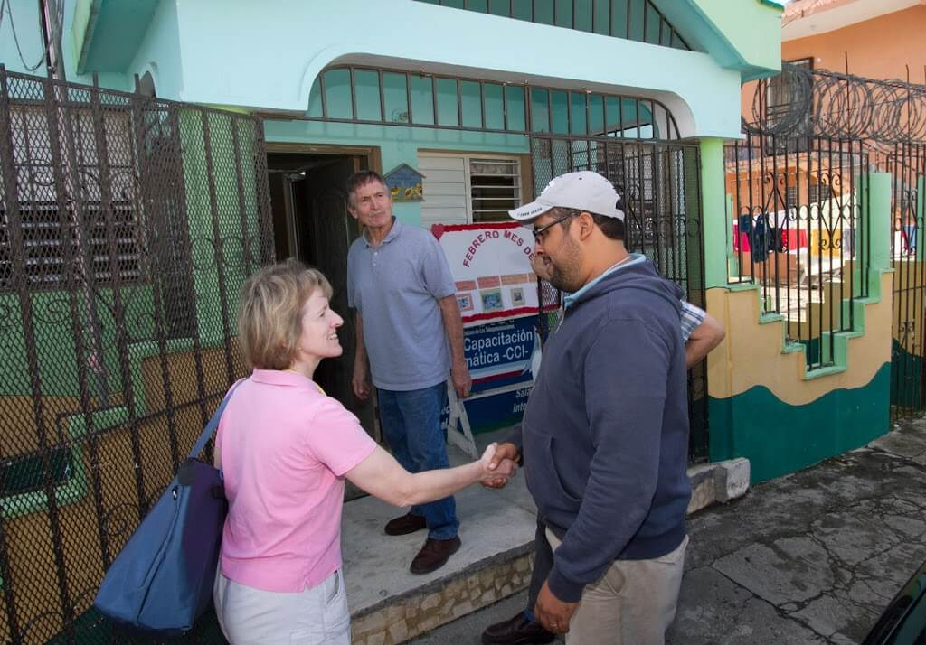 The Rev. Joan Kilian is greeted by Padre Hipólito Fernández Reyna at the entrance to El Buen Samaritano, a day care center in San Francisco de Marcorís. Mission team member Fred Richter is in the background of this photograph.