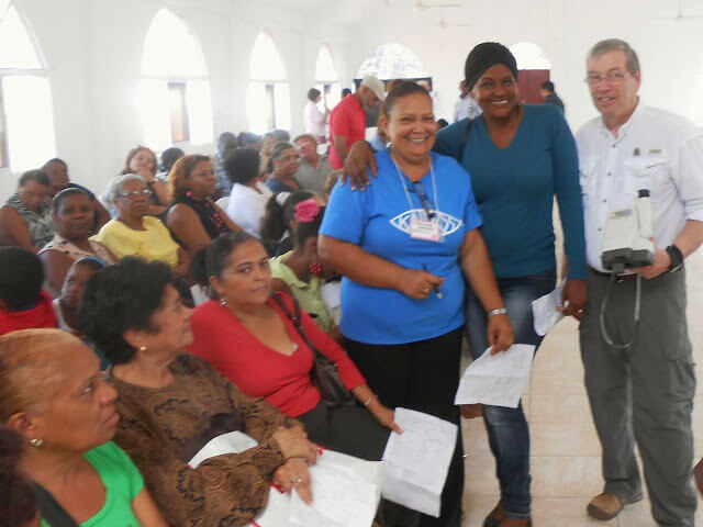 A missioner on the optical mission team with patients in the clinic.