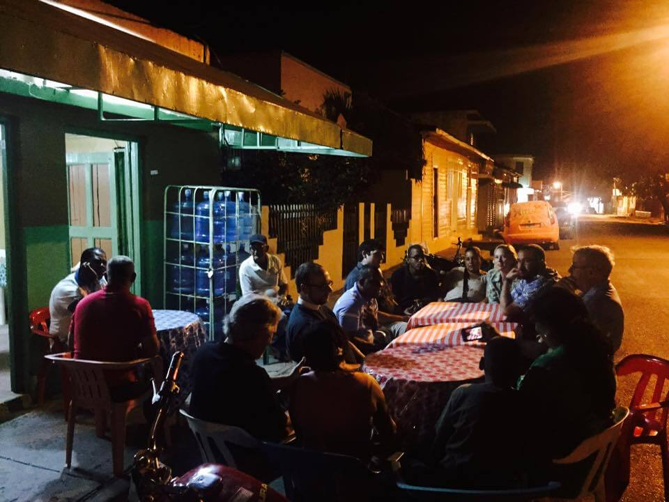 An evening meal at a sidewalk restaurant.