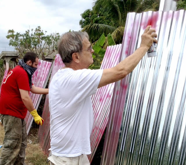 The Rev. David Somerville painting metal roofing panels.