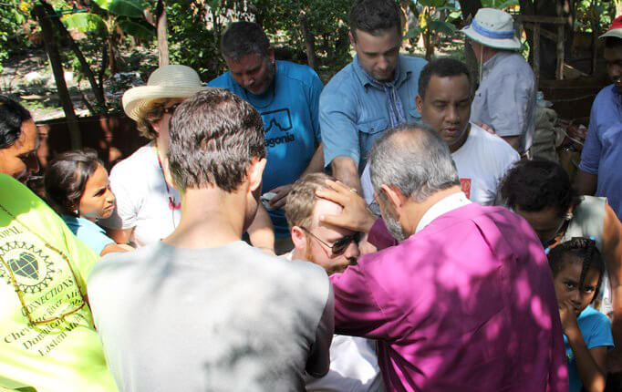 Bishop Holguín (purple shirt, back to camera) blesses the Rev. Lonnie Lacy while other team members and local residents gather around.